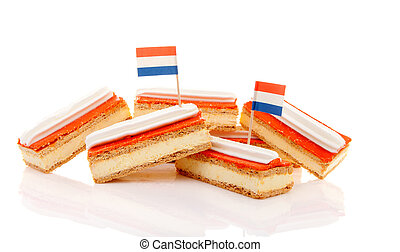 Pile of traditional Dutch pastry called tompouce with flags...