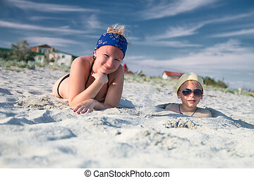 mother and child buried in the sand