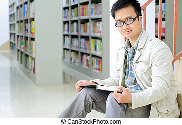 Handsome man sitting and reading in library