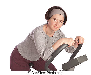 Thick middle-aged woman at the gym on a stationary bike. On...