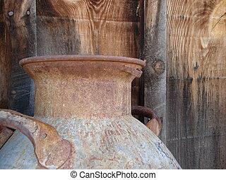 Metal Water Bucket - An old, rusty metal water bucket sits...