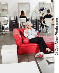 Client Holding Magazine While On Call At Salon - Female...