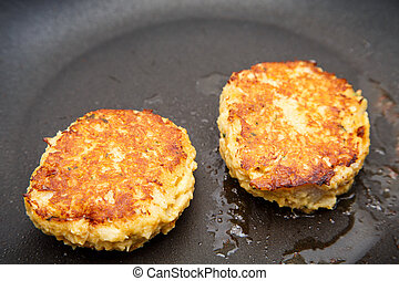 Two Crab Cakes Browning in Saute Pan - Two crab cakes...