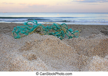 Old Fishing Net on Beach - Worn out green blue rope nylon...