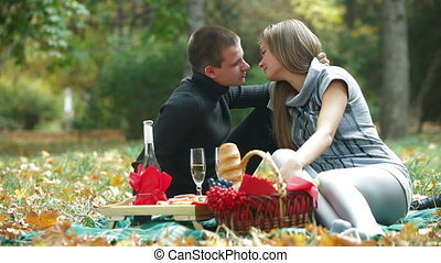 Young loving couple having a picnic in autumn park