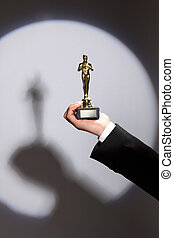 Oscar award in hand - The winner holds in his hand the...