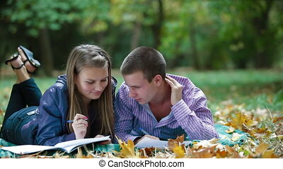Teenage students studying in autumn park