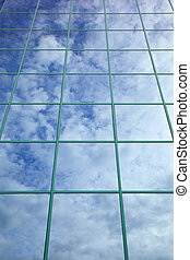 clouds and blue sky reflected in glass facade of office...