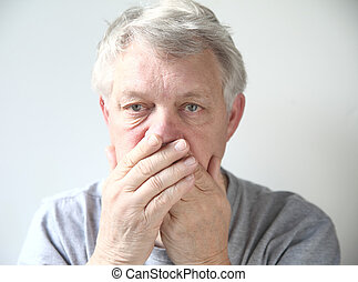 man worried about his bad breath - senior man holds his...