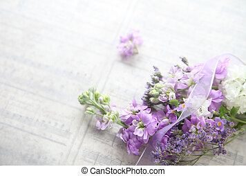 mixed flowers with old music - flowers in lavender shades on...