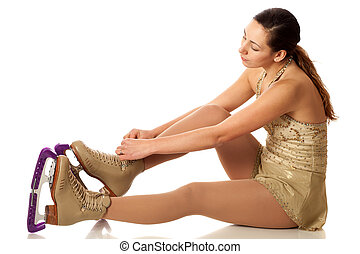 Figure Skater - Figure skater tying skates. Studio shot over...
