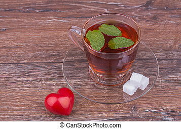 Cup tea with mint on wooden background