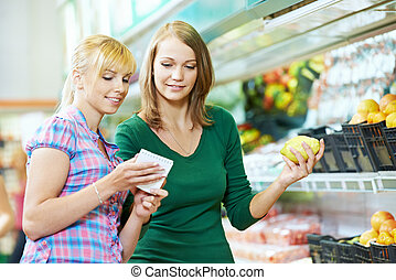 Two women at supermarket fruits shopping - Two woman...