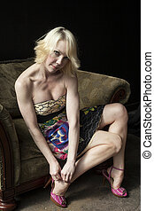 Seated Blonde Woman Adjusts Her Pink Shoes - Seated blond...