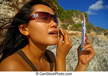 Asian woman applying make-up - Asian woman on the beach,...