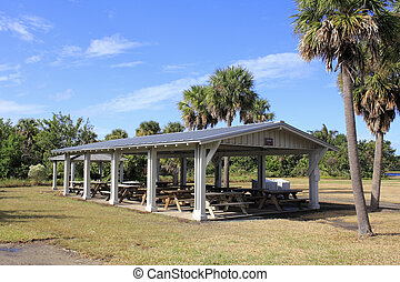 Covered Picnic Tables - A dozen wood picnic tables covered...