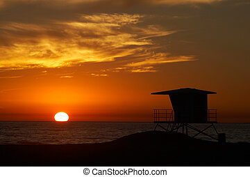 Lifeguard tower - Lifeguard tower with setting sun on the...