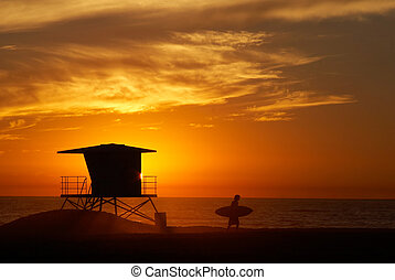 Surfer and lifeguard tower. - Lifeguard tower with setting...