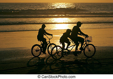 Family riding bikes along the beach at sunset.