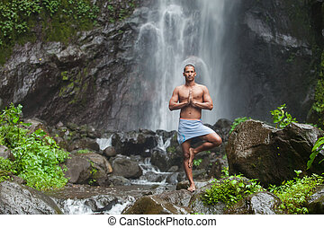 Handsome man at waterfall - Young handsome man enjoying yoga...