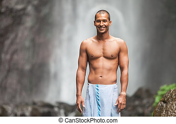 Handsome man at waterfall