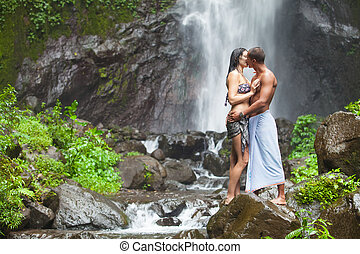Couple at waterfall - Young couple enjoying the freshness of...