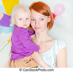 Young mother holding her little daughter