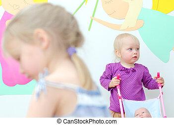 Baby girl with buggy in kindergarten