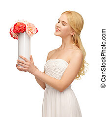 woman with vase of flowers - picture of young and beautiful...