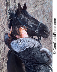 nice women with black horse portrait.