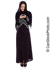 young Arabian woman reading email on smart phone - beautiful...