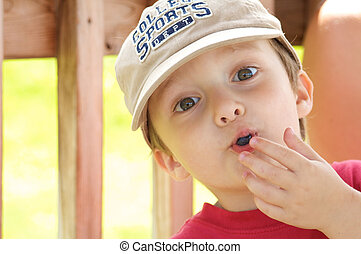 Boy eating blueberry - Cute little boy eating a blueberry