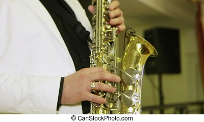 Playing the saxophone - Man in a white suit, playing the...