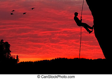 Rock Climber Rappelling Silhouette - Silhouette of a rock...