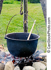 Old pot with a spoon over a fire