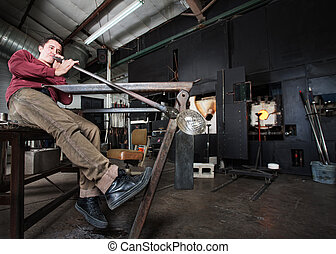 Worker Blowing Glass - Wide angle view of artisan blowing...