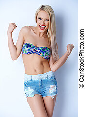 Happy sexy blond girl in short jeans and colorful bikini bra...