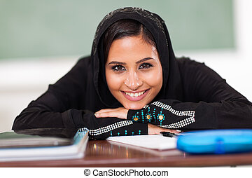 smiling Muslim female high school student in classroom