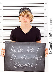 teen boy mug shot - teen boy holding a blackboard criminal...