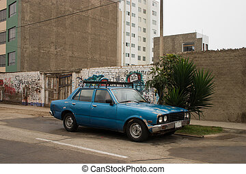 Old bashed up car - in the city of Lima in Peru