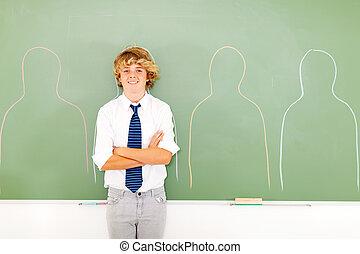 teen boy standing in front of chalkboard