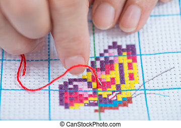 Cross Stitch - Hands of the girl working upon the...