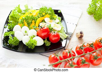 salad with fresh vegetables and quail eggs on a square plate