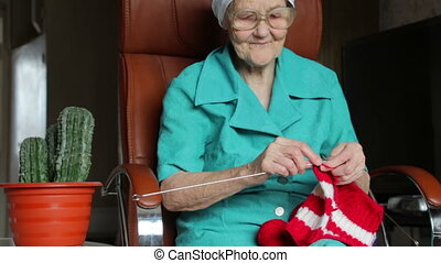 old woman knitting - old woman sitting on chair and knitting