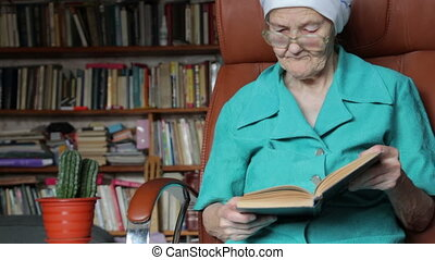 old woman reading book - old woman sitting on chair and...