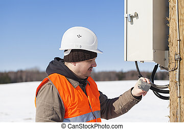 Electrician with electrical cable in the hands near...
