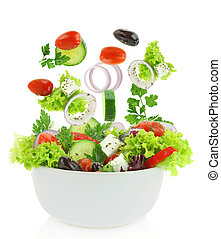 Fresh mixed vegetables falling into a bowl of salad