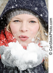 young blond woman blows in a handful of snow - young blond...