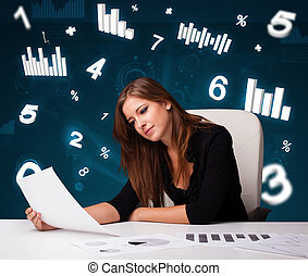 Pretty young businesswoman sitting at desk with diagrams and...