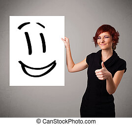 Young woman holding smiley face drawing - Attractive young...